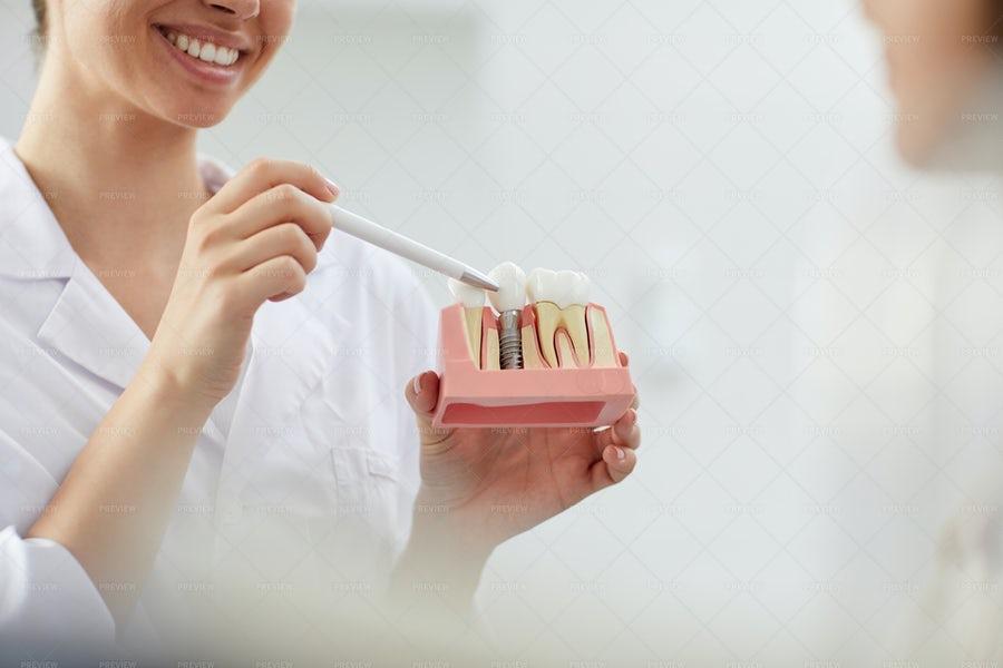 خانم دندانپزشک خندان در حال تشریح ساختار دندان