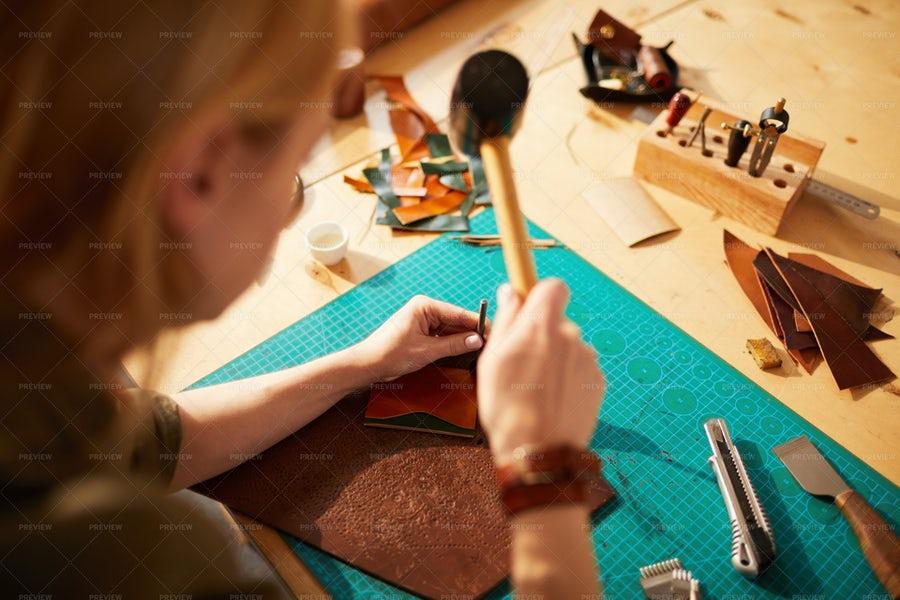 تصویر یک خانم صنعتگر درحال ساخت کیف چرمی از زاویه بالا